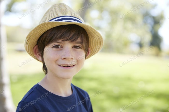 Young schoolboy in a sun hat smiling to camera, portrait
