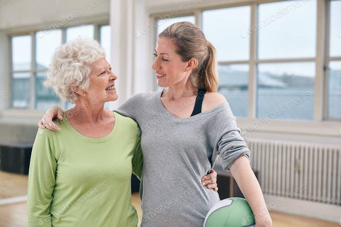 Glückliche Senior Frau mit ihrem Personal Trainer im Fitnessstudio