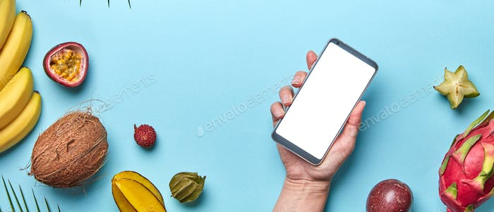 Coconut, lychee, pineapple set of tropical fruits. The girl's hand is holding the phone on a