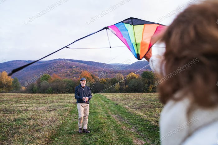 Carefree senior couple flying a kite in an autumn nature.