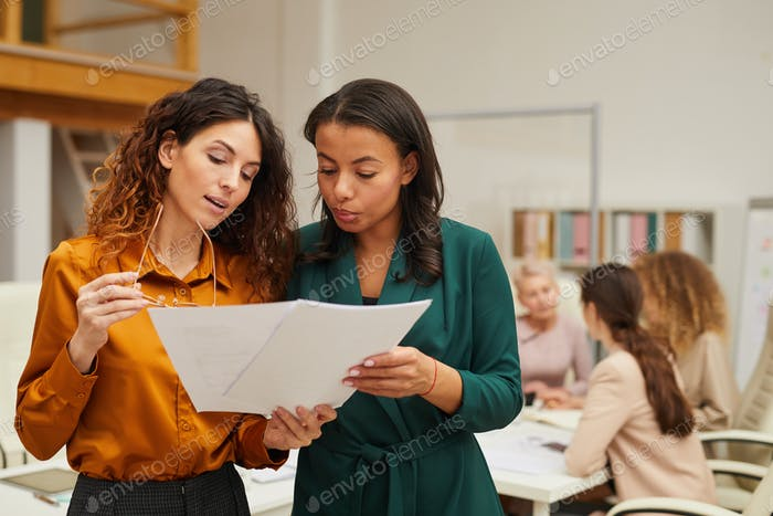 Two Female Designers Looking At Sketches