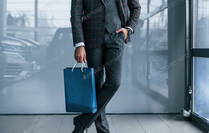 Close up view of businessman in suit standing indoors with blue package