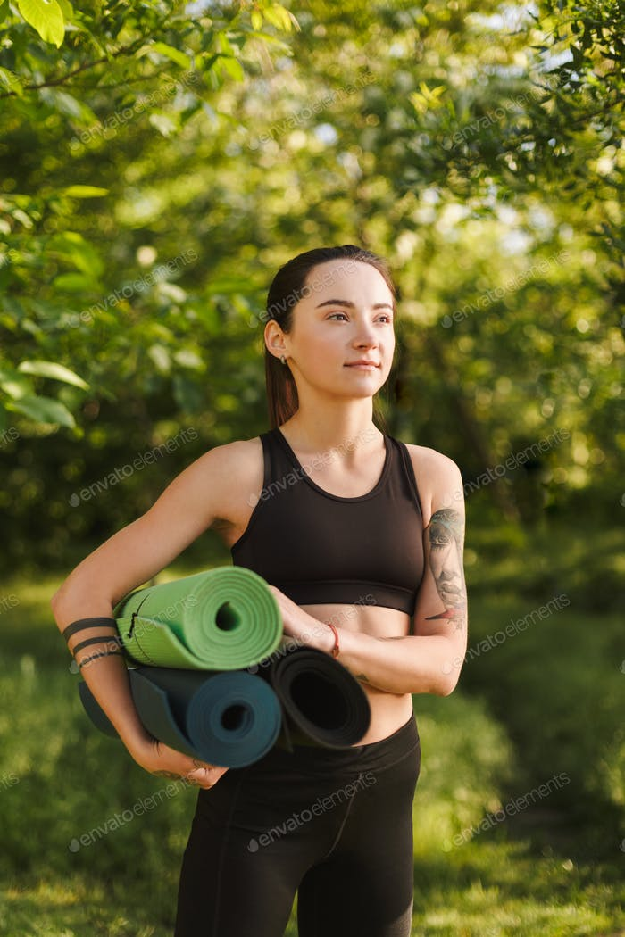 Lady in black sporty top and leggings standing with yoga mats in hands and dreamily looking aside