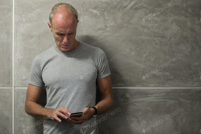 Mature Scandinavian man messaging with phone