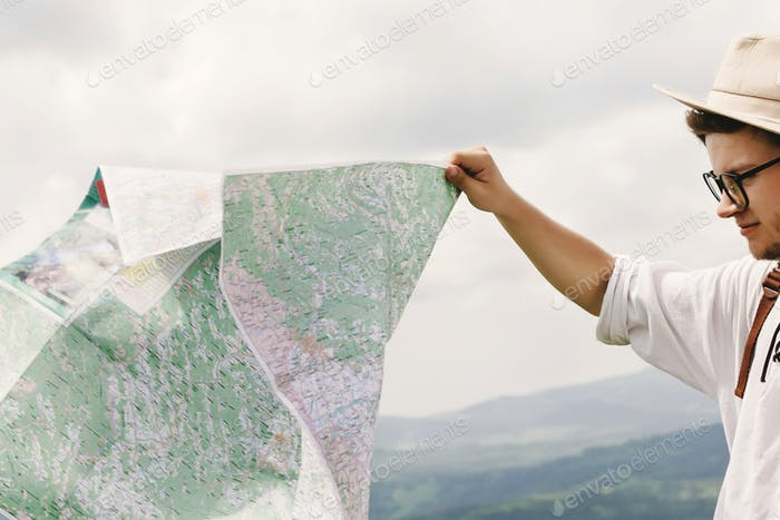 Stylish hipster traveler man holding map and exploring at top of mountains