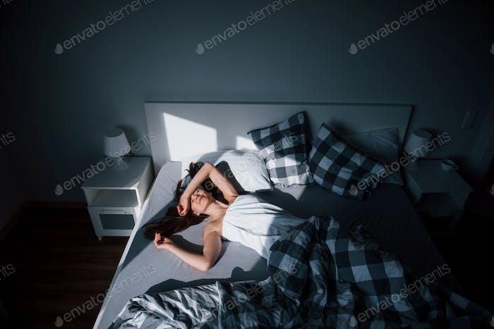 Komfortabler Ort. Hübsche junge Frau liegt morgens auf dem Bett in ihrem Zimmer