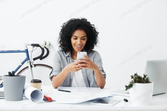 Cheerful young mixed race engineer feeling happy and excited while reading message on smart phone, r