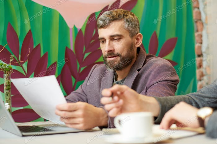 Mature Businessman Working in Cafe