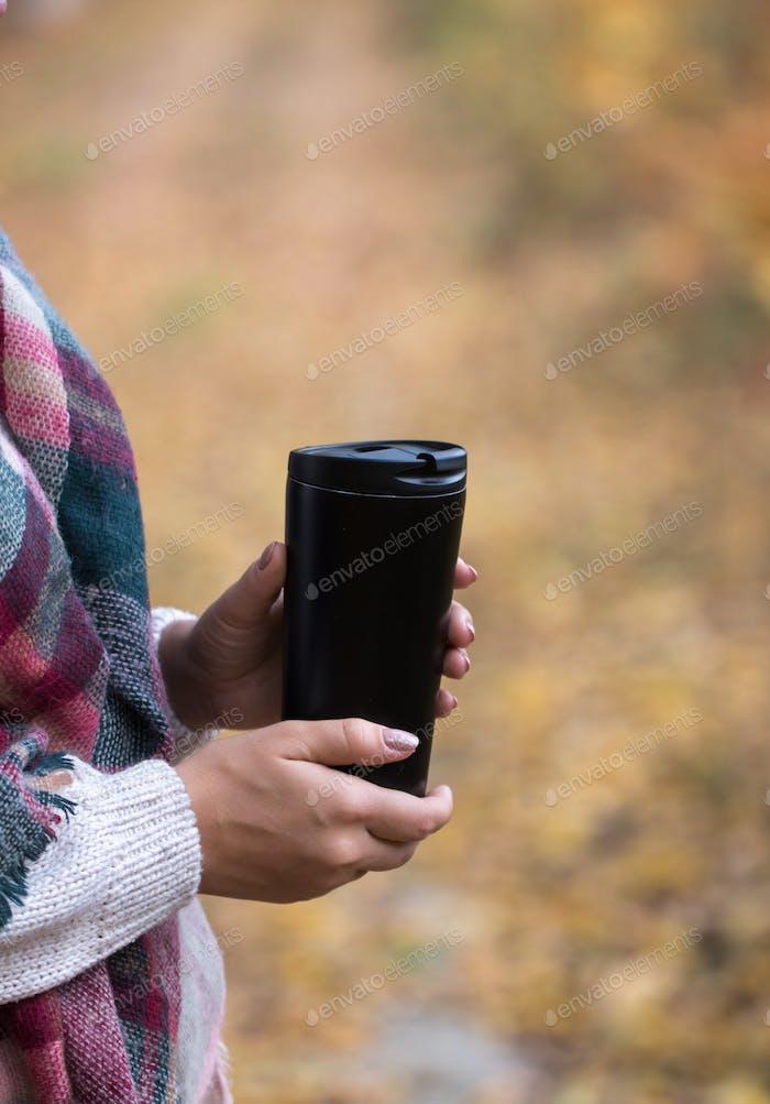 Frau halten Tasse im Wald, Herbstfoto
