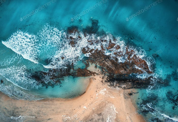 Aerial view of waves, rocks and transparent sea