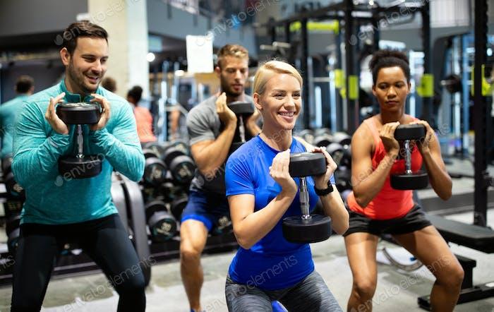 Gruppe von fit Menschen im Fitnessstudio Training. Multiracial Gruppe von Freunden, die gemeinsam arbeiten