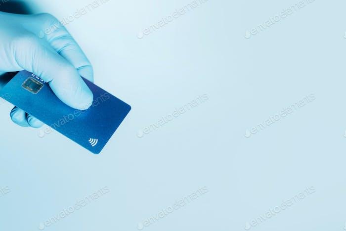 Kontaktloses Zahlungskonzept, Kopierraum. Hand in Schutzhandschuhe halten Kreditkarte mit
