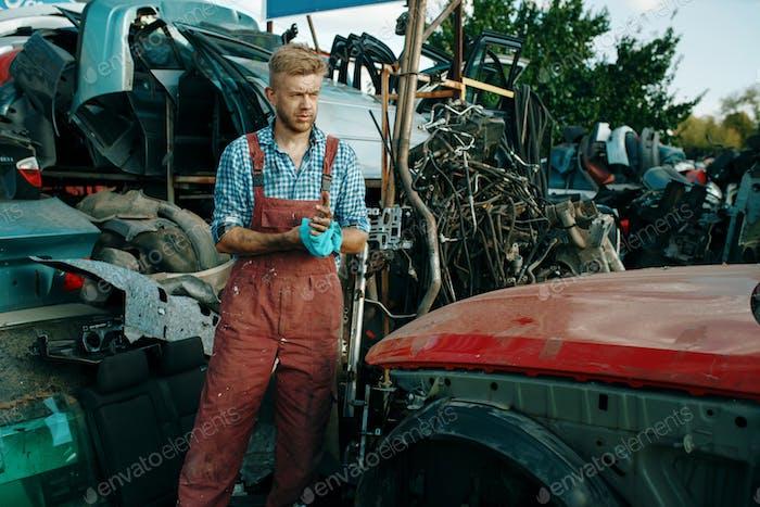 Male repairman with towel on car junkyard