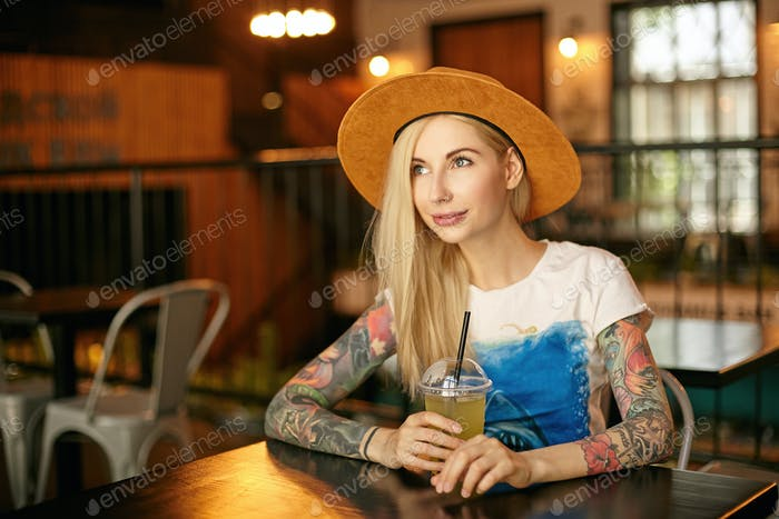 Beautiful young blonde female with tattooes wearing casual clothes