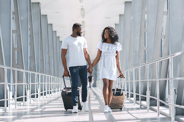 Schwarzes Paar in der Liebe gehen auf Flug Abflug mit Koffern