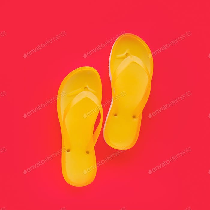 Yellow beach flip flops on neon pink background