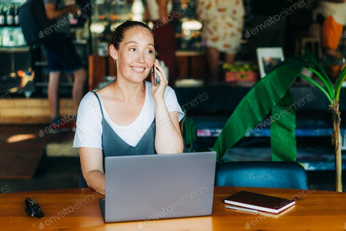 Confident authentic business woman sitting in a coffee shop with a laptop talking on a mobile phone.