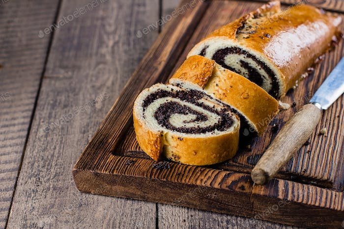 Homemade roll with poppy seeds on wooden board on wooden table background. Copy space