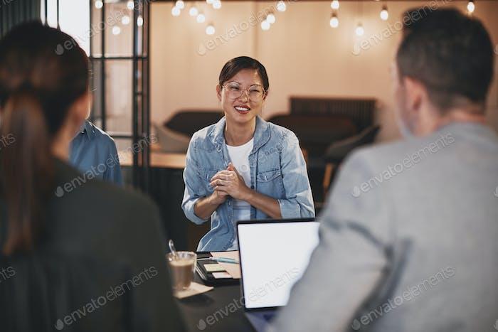 Улыбающаяся азиатская бизнесвумен разговаривает с коллегами во время встречи
