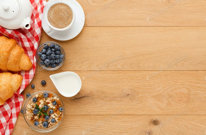 Continental breakfast with croissants and berries on natural wood