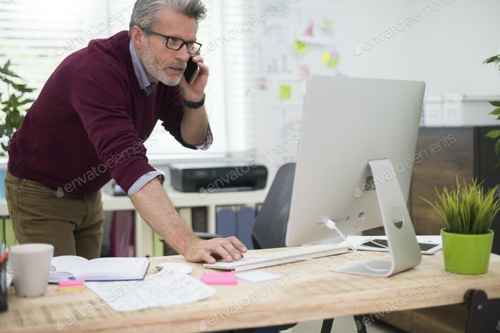 Busy man using telephone and computer simultaneously