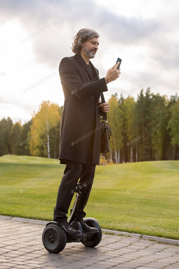 Bearded businessman in black coat using smartphone while standing on gyroscope