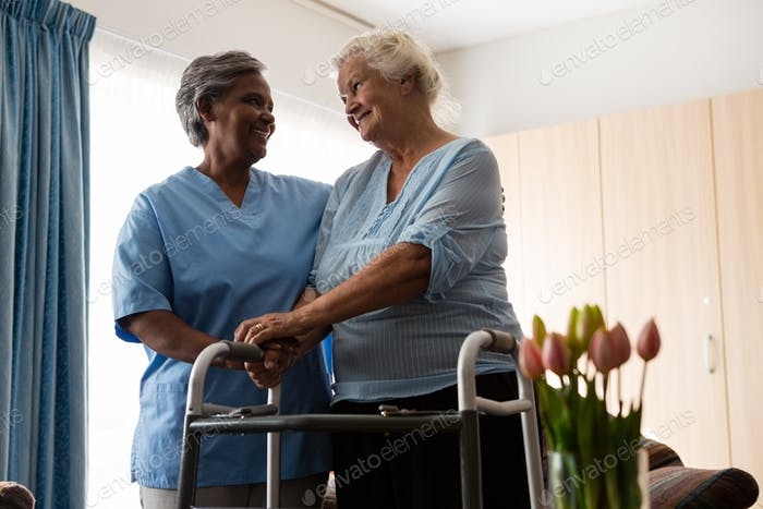 Nurse assisting senior patient in walking with walker