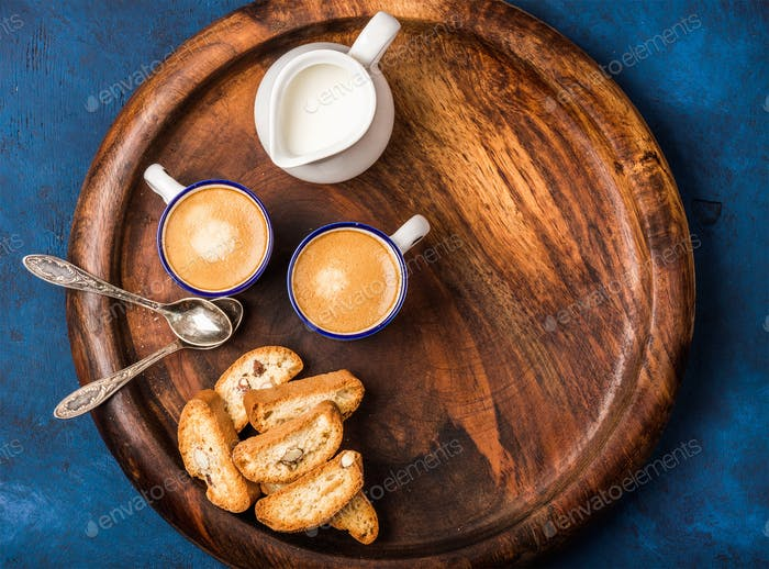 Coffee espresso, cookies and milk on wooden serving round board