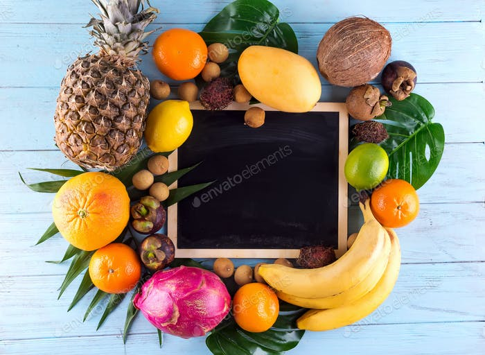Assortment of tropical fruits with leaves of palm trees and and chalk board on blue wooden