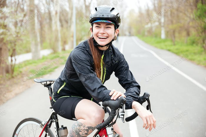 Happy beautiful young woman in bicycle helmet on bike
