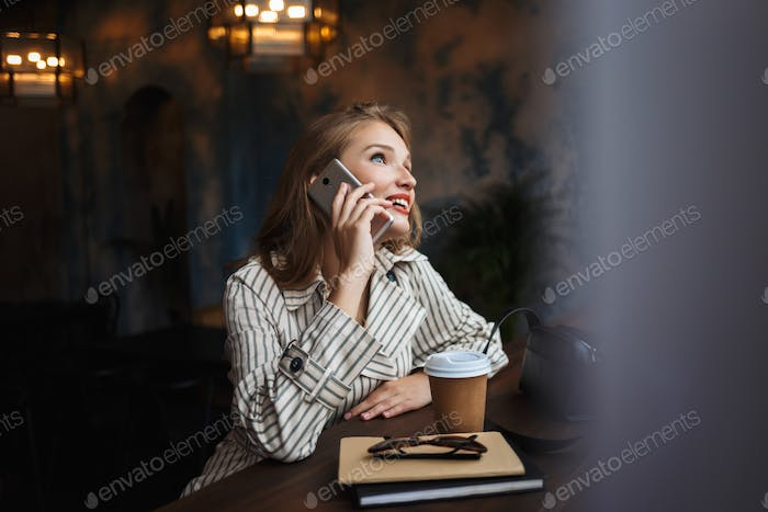Young joyful woman in striped trench coat talking on cellphone h