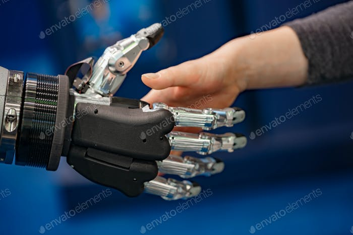 Hand of a businesswoman shaking hands with a Android robot.