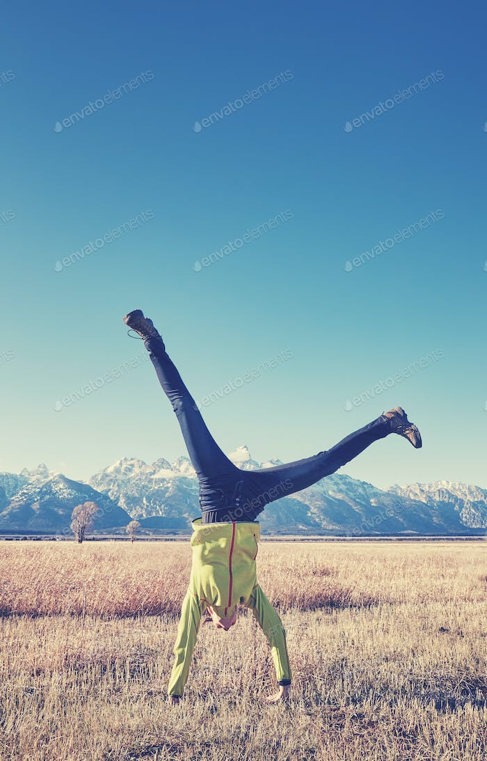Color toned picture of young woman upside down on a meadow.