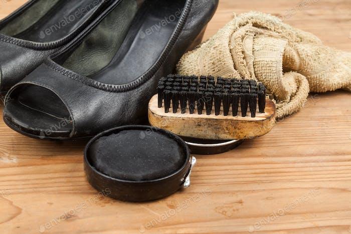 Schuhpolitur mit Pinsel, Tuch und abgenutztem Damenschuh auf Holz