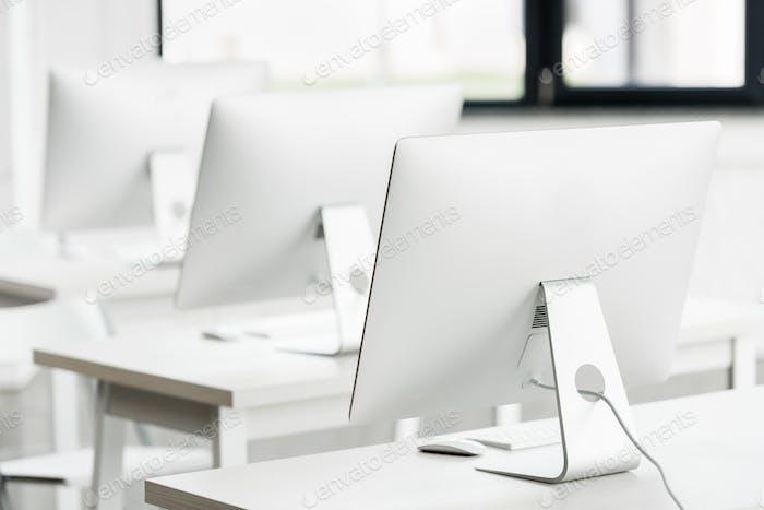 vista de cerca de los monitores blancos de ordenador de pie sobre mesas en clase informática