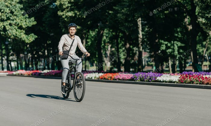 Cheerful young employee with helmet on utility bicycle rides to modern workplace