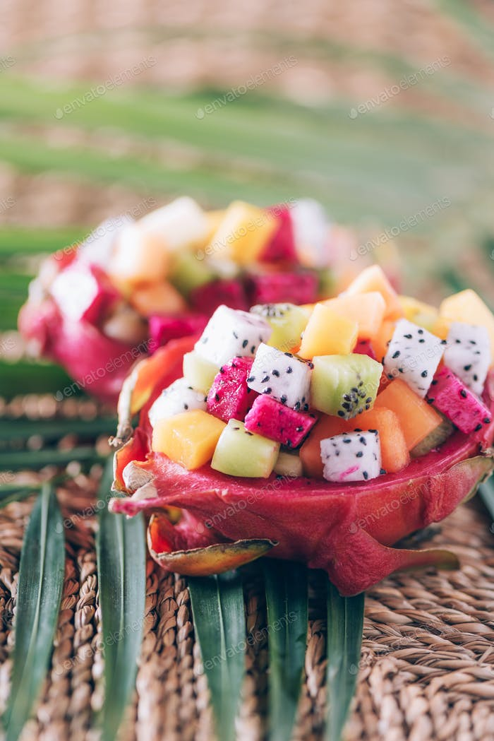 Exotic fruit salad served in half of dragon fruit over palm leaves on rattan background. Copy space