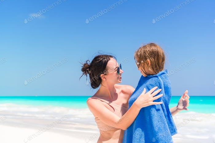 Happy mother and little girl on the beach vacation. Little in towel on the seashore