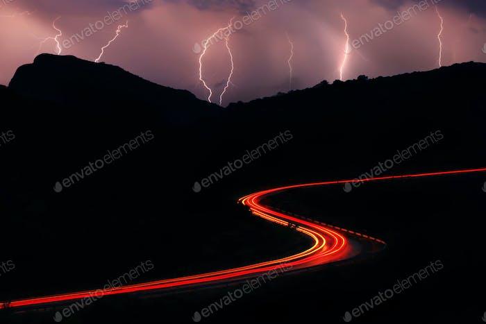 Nachtstraßen in den Bergen mit einem Strom von Autos