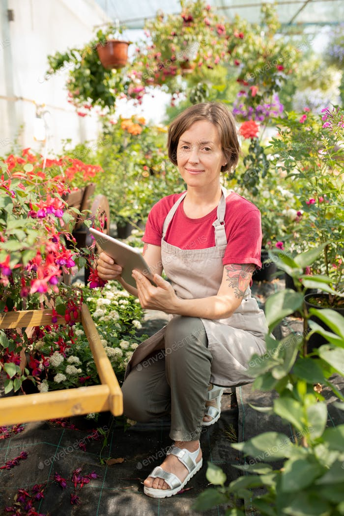 Young female in apron sitting by flowerbed with blooming flowers