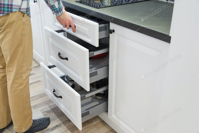Men opensing white kitchen drawers