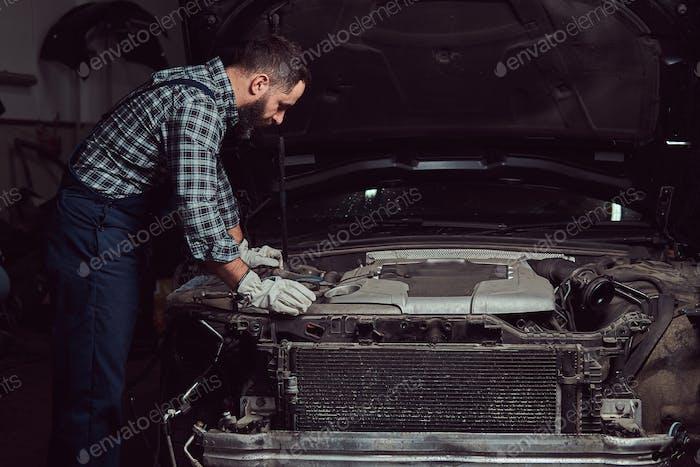 Mechanic man in uniform repairing a car in the garage.