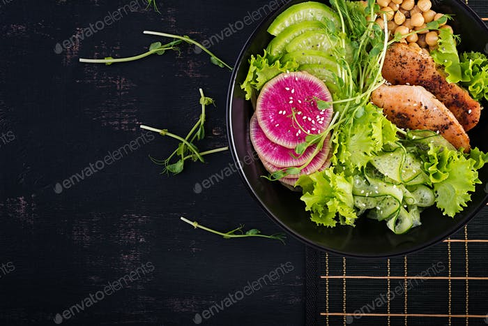Buddha bowl dish with chicken fillet, chickpea, cucumber, radish,  fresh lettuce salad, pea sprouts