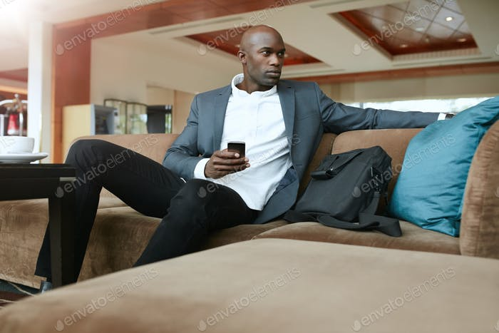 Young business man waiting in hotel lobby