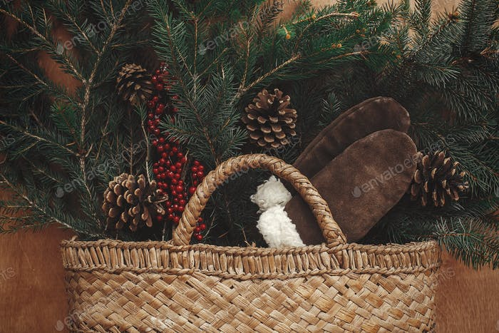 Rustic basket with fir branches,festive cozy gloves, cones and berries on rustic wooden background