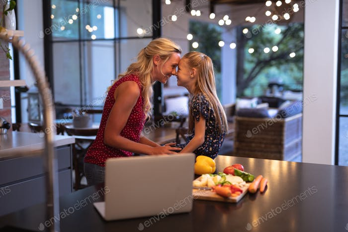 Caucasian woman spending time in the kitchen with her daughter