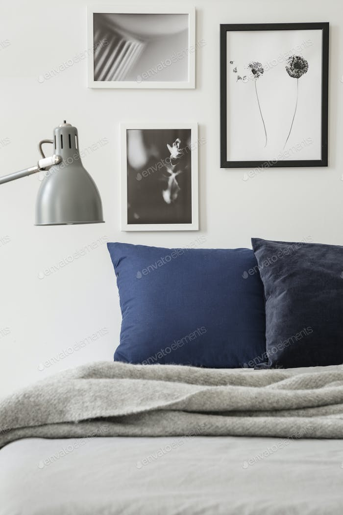 Lamp above grey blanket on bed with cushions in minimal bedroom