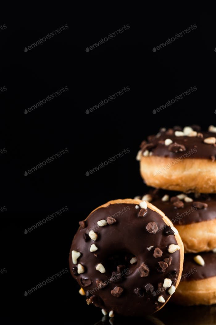 Stack of Chocolate Donuts or Doughnuts on Black Background with Copy Space