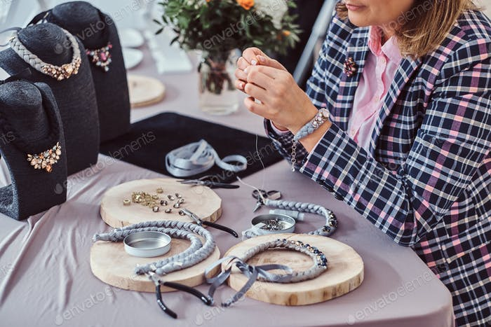 Elegantly dressed woman makes handmade necklaces in jewelry workshop.