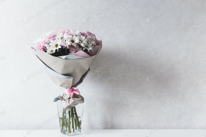 Blumenstrauß aus weißen und rosa Chrysanthemen in Glasvase auf Tisch